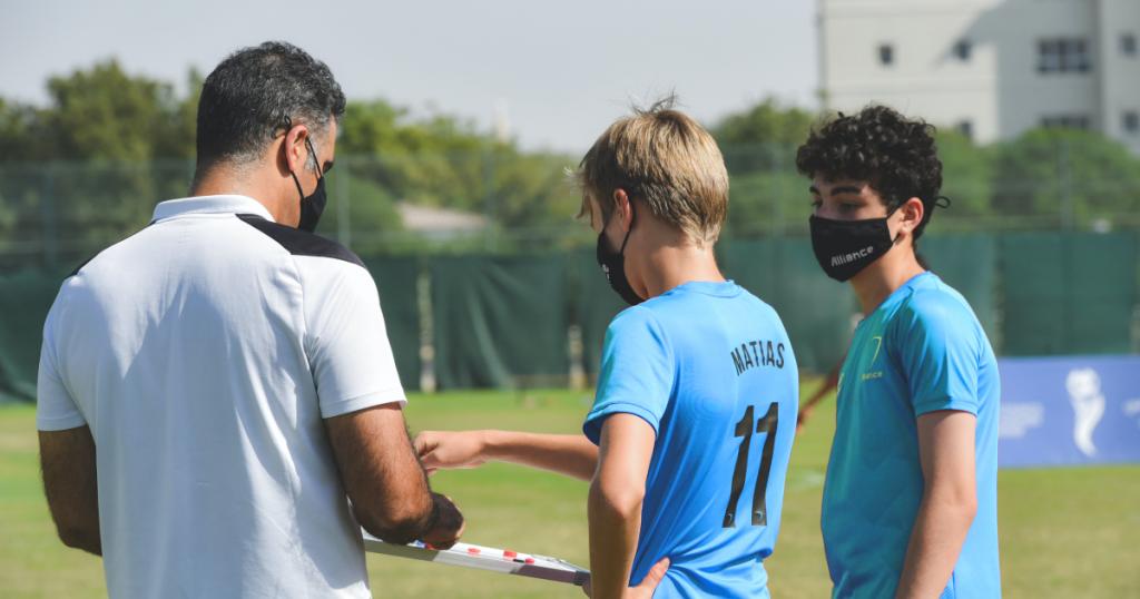 entraîneur montre plan de jeu aux joueurs